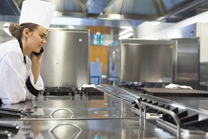 Young pretty chef standing next to work surface phoning