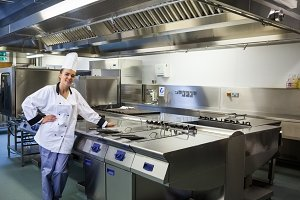 Young content chef standing next to work surface
