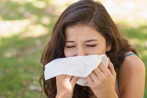Sick young woman using a handkerchief