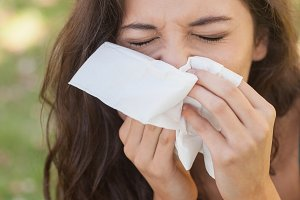 Sick brunette woman using a handkerchief