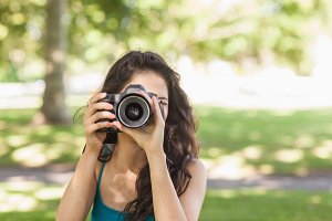 Front view of cute brunette woman taking a picture with her camera