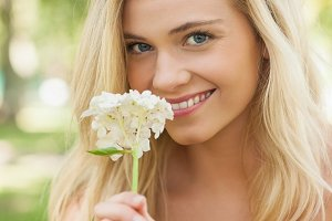 Pretty young woman smelling a white flower