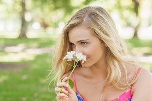 Lovely blonde woman smelling a flower
