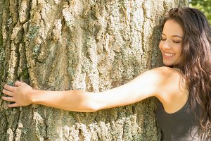 Casual happy brunette embracing a tree with closed eyes