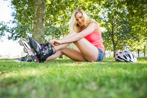 Casual smiling blonde putting on roller blades