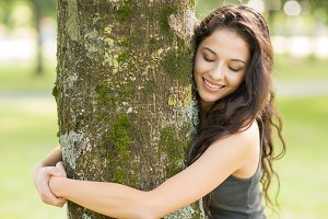 Casual cheerful brunette embracing a tree with closed eyes
