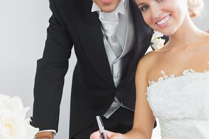 Portrait of pretty young couple signing wedding contract