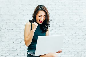 Young Asian business working woman winning and having success with laptop
