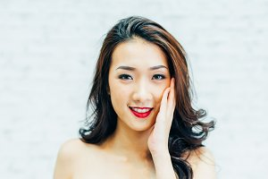 Asian woman rubbing her face in beauty shot with blurred white wall background