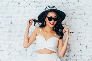 Young happy Asian woman smiling in fashionable dress and sunglasses and summer hat over white brick wall with copy space