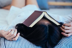 Female teen falls asleep while reading the book - book on top of her face