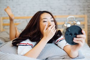 Asian woman yawning and looking at the alarm clock on the bed