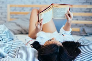Woman reading the book on her bed in the morning at home
