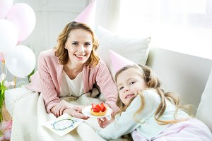 mother and daughter holding cake