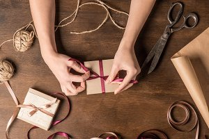 hands tying ribbon on gift