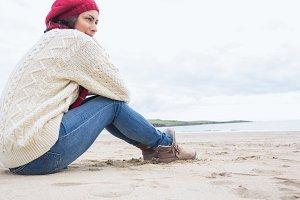 Woman in stylish warm clothing sitting at beach