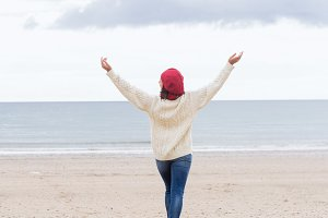 Woman in casual warm wear stretching arms on beach