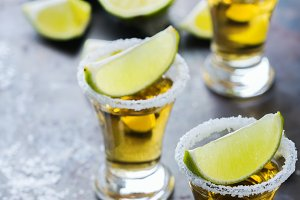 Golden mexican tequila shot with green lime and salt