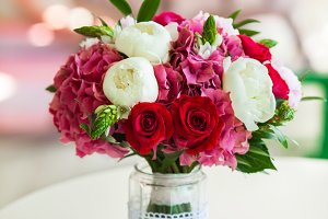 Wedding bouquet roses and peonies in glass vase on table
