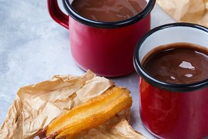 Traditional spanish churros with hot chocolate in a mug