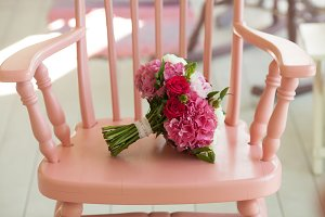 Beautiful wedding bouquet roses and peonies on pink chair