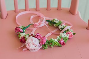 Beautiful wreath with roses and peonies on pink chair