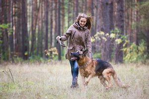 Young attractive woman playing with German Shepherd dog outdoors in the autumn park