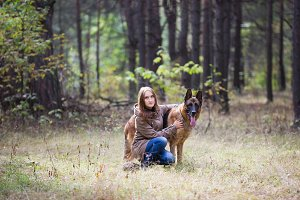 Young attractive woman posing with German Shepherd dog outdoors in the autumn park