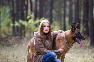 Young attractive woman posing with German Shepherd dog outdoors in the autumn park, close up