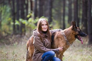 Young attractive woman posing with German Shepherd dog and smiling outdoors in the autumn park, close up