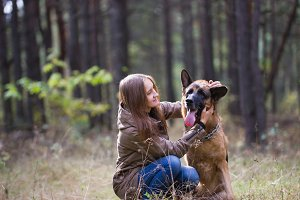 Young attractive woman playing with German Shepherd dog outdoors in the autumn park, close up