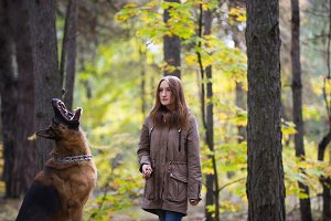 Young cute woman playing with German Shepherd dog outdoors in the autumn forest, close up