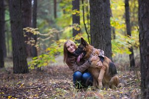 Young cute woman hugging a German Shepherd dog outdoors in the autumn forest