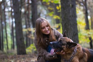 Young cute smiling girl playing with German Shepherd dog outdoors in the autumn forest