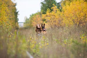 Attractive young woman walking wuth her dog German shepherd at autumn forest, near rail way - wide angle