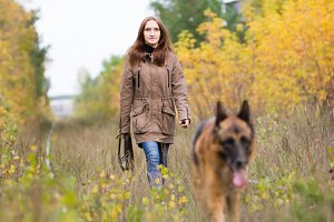 Attractive young woman walking with her dog German shepherd at autumn forest, near rail way - the girl is in focus