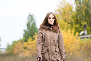 Portrait of young cute woman in fall autumn park. Beautiful caucasian girl walking in forest
