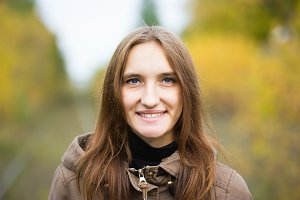 Portrait of young cute woman in fall autumn park. Beautiful caucasian girl walking in forest, close up
