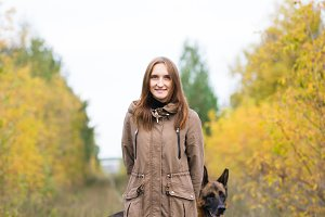 Young cute woman with german shepherd dog posing in autumn forest near rail way