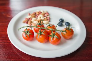 Cherry tomatoes on white bowl with nuts - food background