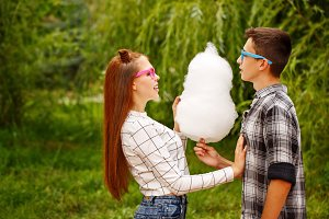 Loving couple teens eat cotton candy