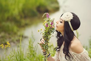 Boho Girl sniffing wildflowers