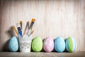 Pastel Easter eggs and brushes in a rustic cup