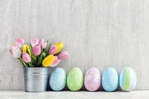 Easter eggs and a spring bouquet of tulips on a wooden table.