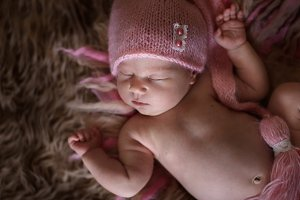 Sleep newborn in pink knitted cap