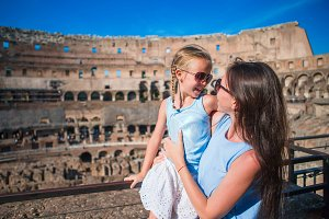 Family in Coliseum in Rome, Italy. Mother and little happy girl at famous place in Europe