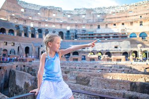 Little girl in Coliseum, Rome, Italy. Cute kid looking at famous places in Europe