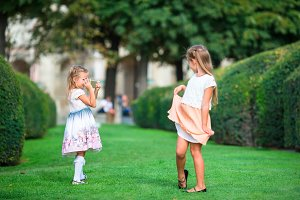 Little adorable girls outdoors at summer time on european vacation in the garden of the Tuileries