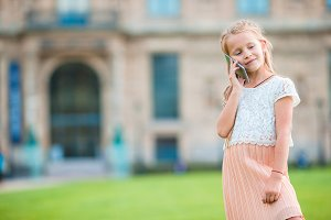 Adorable little girl with phone in Paris during summer vacation
