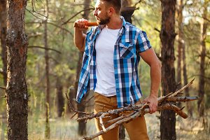 Lumberjack with an ax and firewood